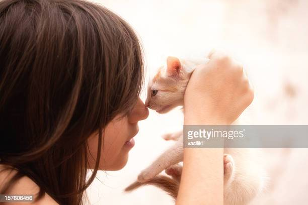 Girl and cat rubbing noses