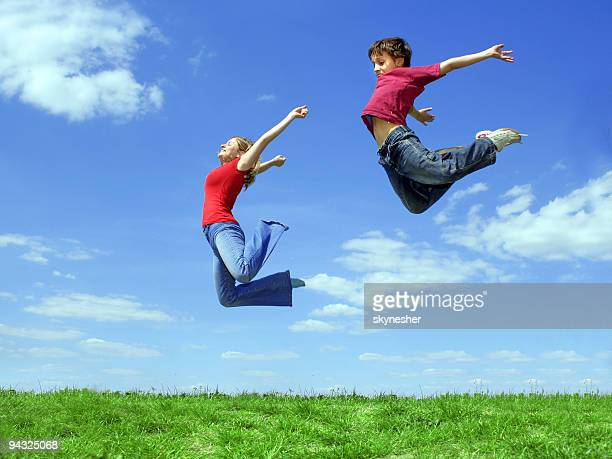 Girl and child jumping on meadow