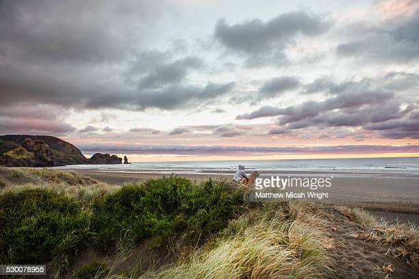 a girl and dog at the surf beach of piha. - auckland stock pictures, royalty-free photos & images