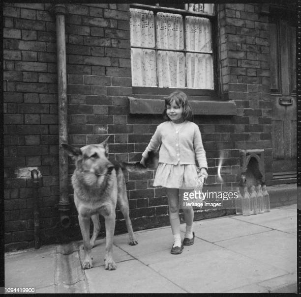 Girl and dog, Middleport, Burslem, Stoke-on-Trent, Staffordshire, 1965-1968. A young girl and an Alsatian dog standing on the pavement outside a...