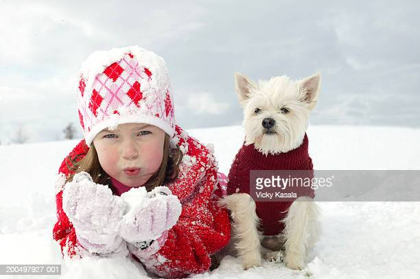Girl (5-7) and dog on snowy hillside, portrait, low angle view