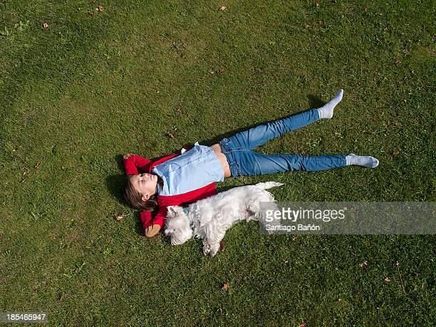 Girl and dog taking a nap at garden