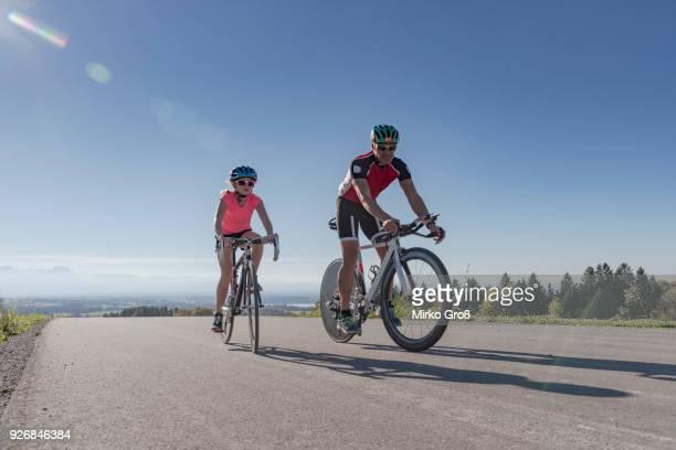 girl and father cyclists cycling on rural road - bicicletta da corsa foto e immagini stock