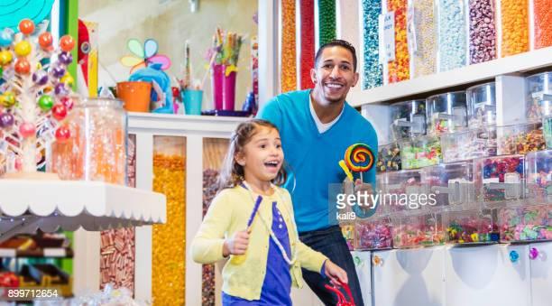 Mädchen und Vater im Süßwarenladen