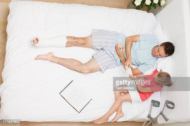 chica y padre sentar en la cama con vista de la tarjeta - pierna escayolada fotografías e imágenes de stock