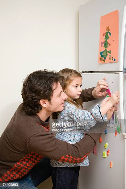 Girl and father putting picture on refrigerator