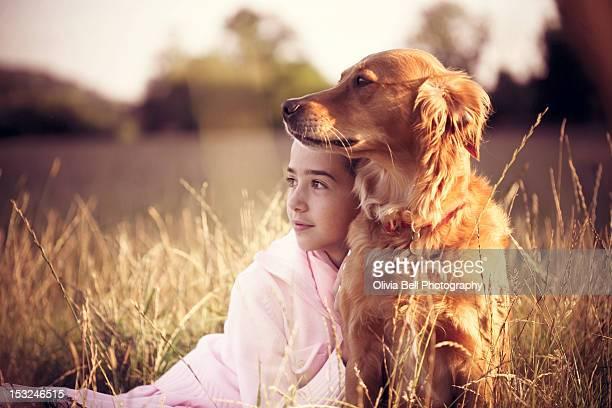 Girl and golden retriever cuddling