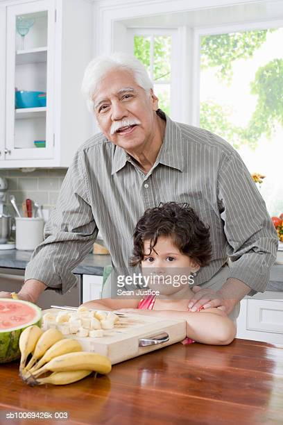 girl (6-7 years) and grandfather preparing food in kitchen, portrait - 65 69 years stock pictures, royalty-free photos & images