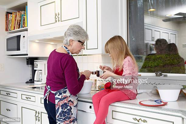 Girl and grandmother looking into saucepan at kitchen counter