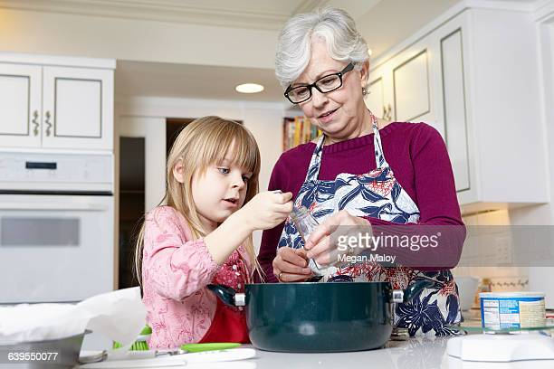 Girl and grandmother measuring salt for cooking