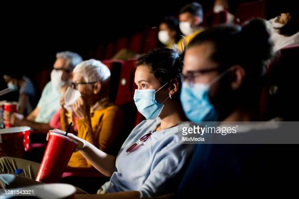 girl and her boyfriend wearing face masks while watching a movie at the cinema - film industry stock pictures, royalty-free photos & images