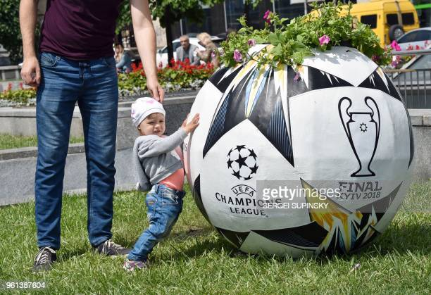 TOPSHOT A girl and her father stand next to a flowerpot shaped like a football ball on Independence Square in Ukrainian capital of Kiev on May 22...