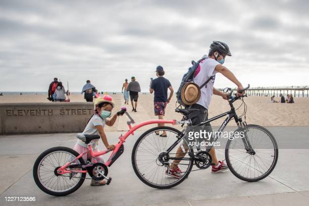 Girl and her father wear facemasks while they push their bikes in Hermosa Beach, Los Angeles, California, on July 14, 2020. - California's Governor...