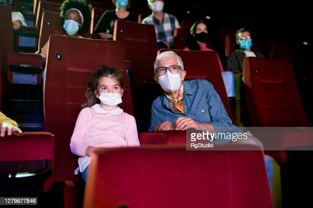girl and her grandma wearing protective face masks and enjoying at the cinema - theatrical performance stock pictures, royalty-free photos & images