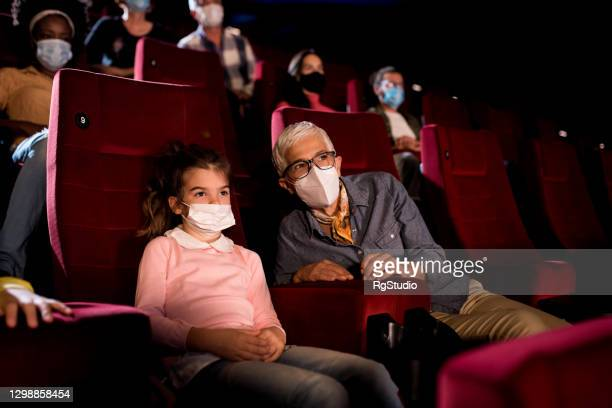girl and her grandma wearing protective face masks and enjoying the film at the cinema - film premiere stock pictures, royalty-free photos & images