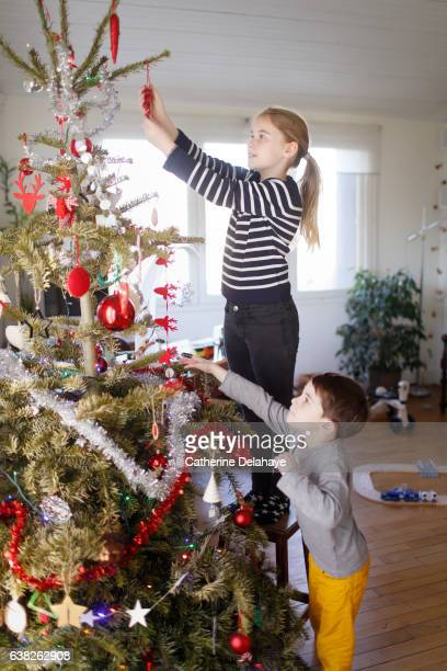 A girl and her little brother decorating the Christmas tree