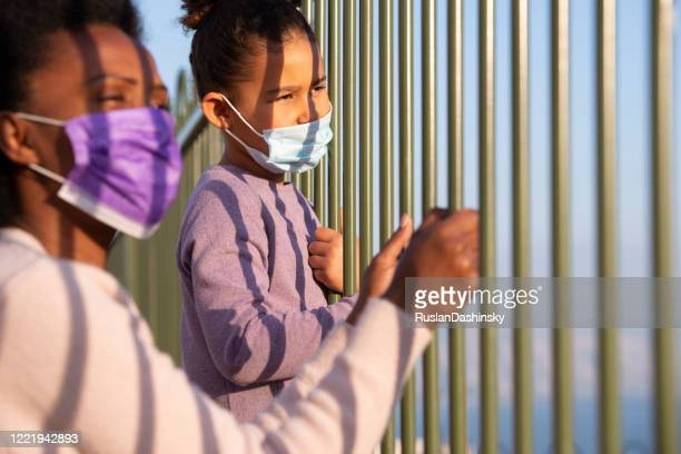 girl and her mother in face masks looking away through the fence bars. coronavirus pandemic concept. - child behind bars stock pictures, royalty-free photos & images