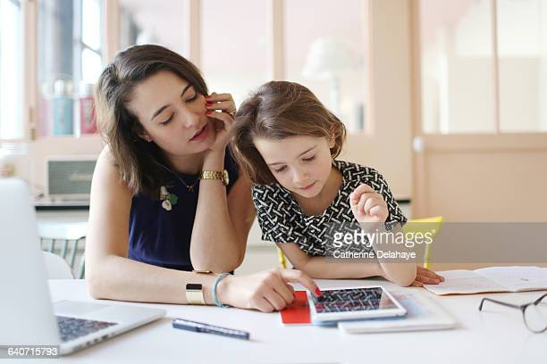 A girl and her mum with a tablet in the kitchen