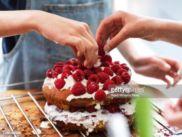 girl and her sister baking a cake, decorating cake with fresh cream and raspberries at kitchen table, cropped view of hands - baking stock pictures, royalty-free photos & images