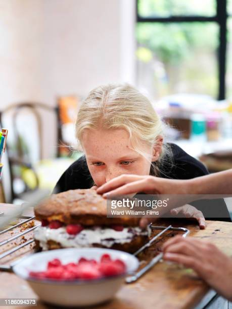 girl and her sister baking a cake, putting on top layer at kitchen table - anticipation stock pictures, royalty-free photos & images