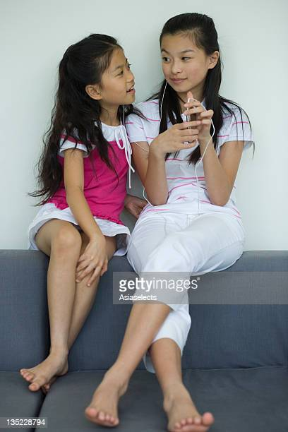girl and her sister listening to an mp3 player - little girls bare feet stock photos and pictures