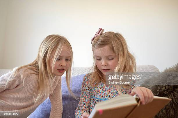 Girl and her sister reading in living room