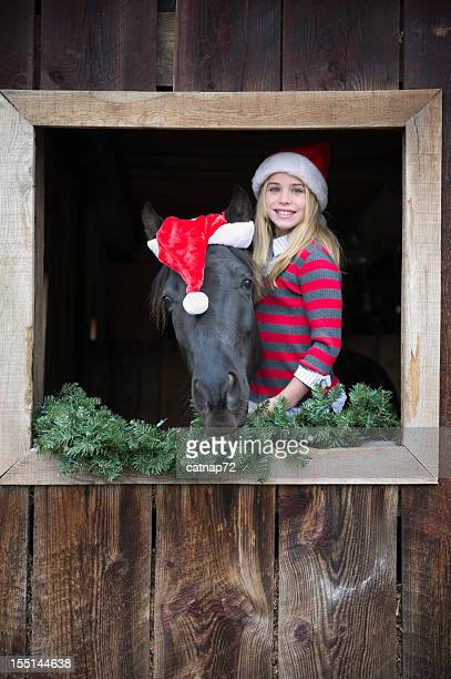 girl and horse in santa christmas hats at barn window - christmas horse stock pictures, royalty-free photos & images
