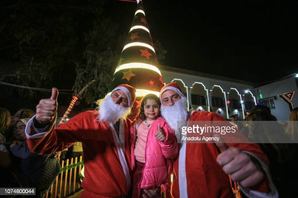 A girl and men with Santa Claus costumes pose for a photo as people gather around an illuminated christmas tree at yard of Christian Youth...