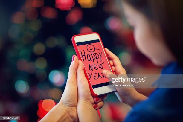 Mädchen und Mutter sind Sedning Happy New Year Zeichnung zu vermissten Vater mit Handy