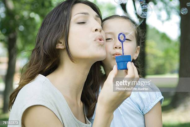Girl and mother blowing bubbles together
