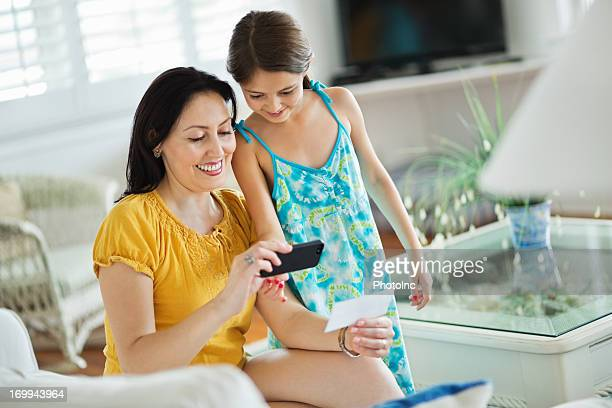 Girl And Mother Depositing Check Through Smart Phone