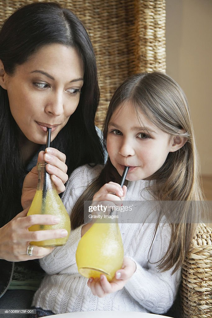 Girl (8-9) and mother drinking juice : Stockfoto