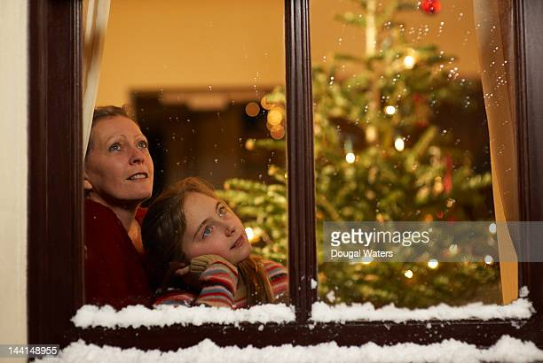 Girl and mother gazing out of window at christmas.