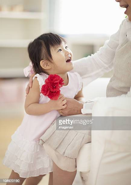 Girl and mother holding carnation flowers