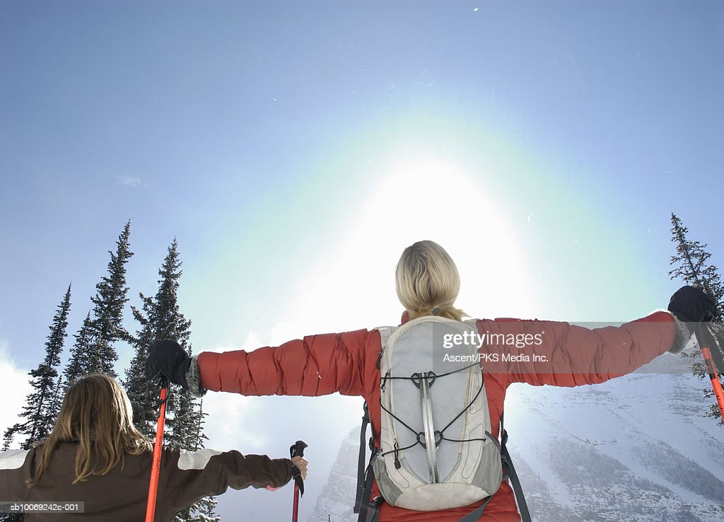 Girl (12-13) and mother holding ski poles looking at sun, arms out, rear view : Stockfoto