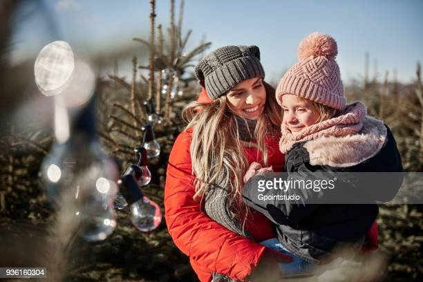 Girl and mother looking at forest christmas tree lights