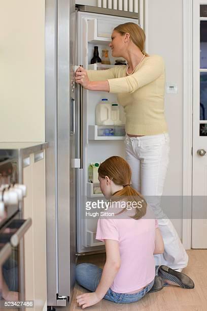 girl and mother looking in refrigerator - hugh sitton bildbanksfoton och bilder