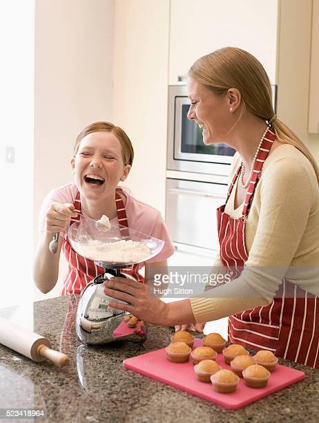 girl and mother making cupcakes - hugh sitton stock-fotos und bilder