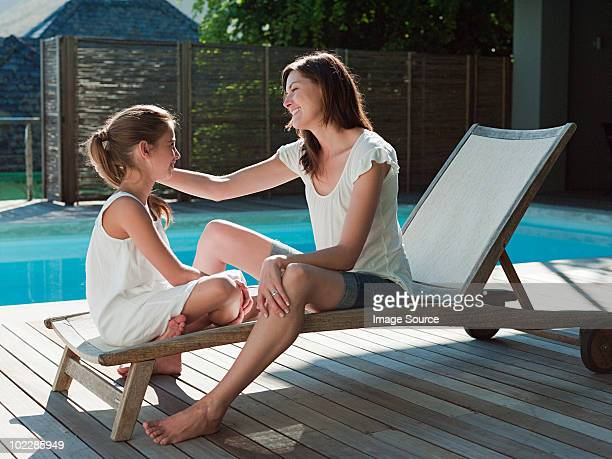 Girl and mother on lounge chair by swimming pool