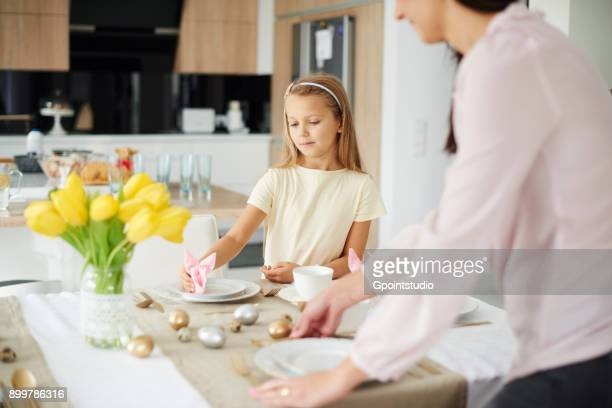girl and mother preparing place settings at easter dining table - happy easter mom stock pictures, royalty-free photos & images