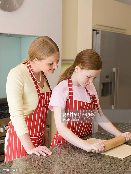 girl and mother rolling out cookie dough - hugh sitton stock pictures, royalty-free photos & images
