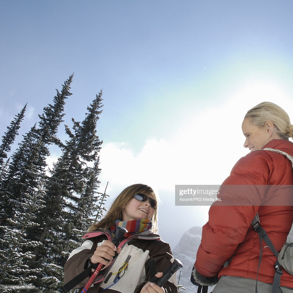 Girl (12-13) and mother skiing, smiling, low angle view : Stockfoto