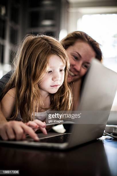 girl (6yrs) and mother using laptop - kind im grundschulalter stock-fotos und bilder