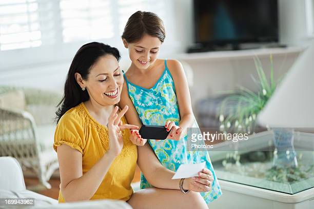 Girl And Mother Using Smart Phone To Deposit Check