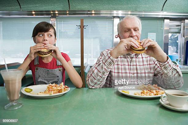 girl and old man eating burgers in a diner - diner stock pictures, royalty-free photos & images