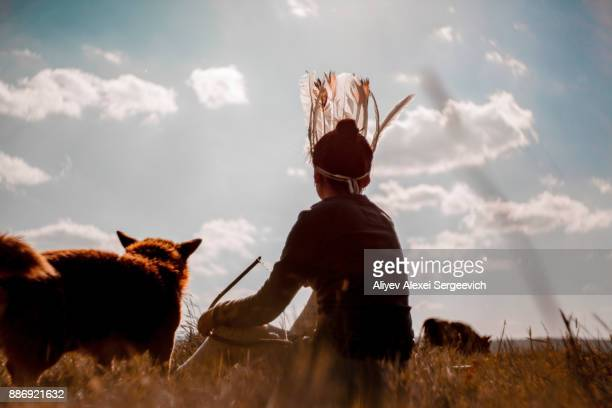 Girl and pet cat on grass looking at cow in distance