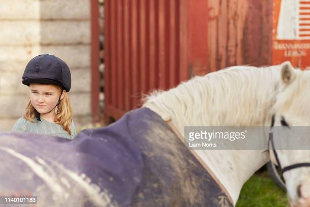 girl and pony looking over their shoulder at stable - pony stock pictures, royalty-free photos & images