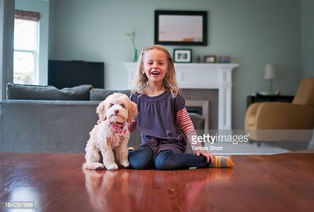 Girl and Puppy Sitting on Floor Together