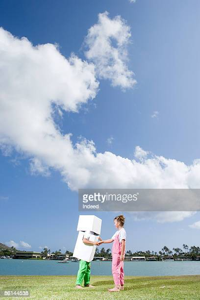 Girl and robot shaking hands on grass