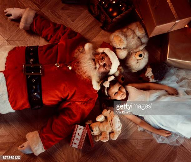 Girl and santa lie on the floor